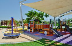 Delma Park - well equiped playground for children. Playground equipped with train toy shaded under tend  standing on violet floor and roundabout carrousel with Stock Photos