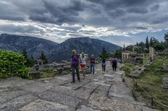 Delphi, Phocis / Greece. Tourists following the Sacred Way in the archaeological site of Delphi Royalty Free Stock Photo