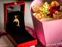 Delphin-Goldanhänger und -rose Stockfoto