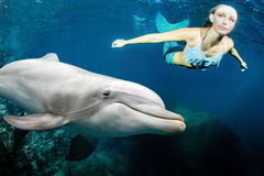 Delphin Underwater trifft eine blonde Meerjungfrau Stockbild