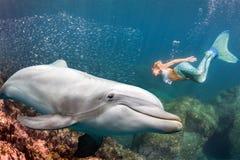 Delphin Underwater trifft eine blonde Meerjungfrau Stockfotos