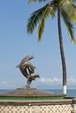 Delphinstatue- und -palme Stockbilder