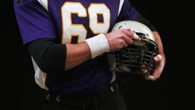 Αμερικανικό ποδόσφαιρο Κράνος εκμετάλλευσης φορέων αμερικανικού ποδοσφαίρου και με τα δύο χέρια Χέρια που κρατούν μια κινηματογρά απόθεμα βίντεο