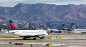 Delta Airline  and Salt Lake City Downtown. Salt Lake City Downtown view from the Salt Lake City International Airport. A Delta Airliner Airbus 320 preparing for Royalty Free Stock Photos