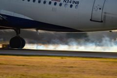 Delta Airlines airplane landing on a runway with tire smoke stock photo