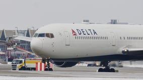 Delta Airlines die taxi in de Luchthaven van München, sneeuw doen stock videobeelden