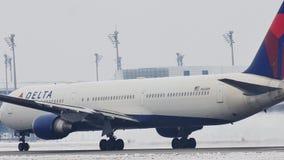 Delta Airlines die van de Luchthaven van München, sneeuw opstijgen stock videobeelden