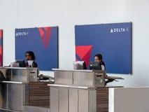Delta Airlines kontrollerar in linjen för passagerare och bagage på Reagan National Airport arkivfoto