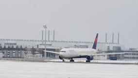 Delta Airlines que hace el taxi en el aeropuerto de Munich, nieve almacen de metraje de vídeo
