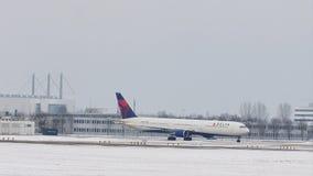 Delta Airlines som gör taxien i den Munich flygplatsen, snö stock video