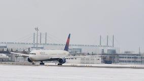 Delta Airlines stor fågel som gör taxien i den Munich flygplatsen, snö lager videofilmer