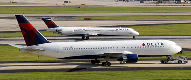 Delta airplanes. Two Delta planes, one on top of the other, both on runways,  one being towed Stock Image