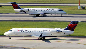 Delta Connection, regional jets. Two delta Connection, regional, commuter planes taxiing in opposite  directions Stock Photo