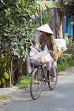 DELTA DE MEKONG, VIETNAME - EM MAIO DE 2014: Ciclagem com chapéu vietnamiano Imagens de Stock
