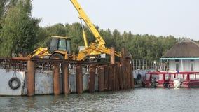 DELTA DI DANUBIO, ROMANIA SETTEMBRE 2015 Escavatore resistente che spinge le colonne del ferro per sostenere il pontone 4K video d archivio