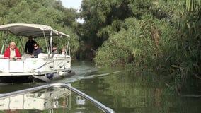 DELTA DI DANUBIO, ROMANIA SETTEMBRE 2015 Turisti in una barca che esce da una regione selvaggia del fiume 4K archivi video