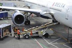 Delta-Fluglinien-Fläche, die mit Fracht geladen wird stockfoto