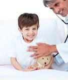 delta i pojkekontrollen little läkarundersökning som ler upp Royaltyfri Fotografi