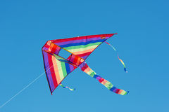 Delta kite in the sky. Rainbow colored kite flying in the blue sky Stock Photos