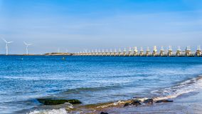 The Delta Works Storm Surge Barrier and Wind Turbines at the Oosterschelde viewed from Banjaardstrand royalty free stock image
