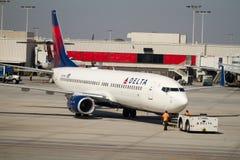 Deltadie vliegtuig van poort wordt geduwd stock afbeelding