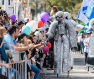 Deltagare av den årliga karnevalet av Adloyada som går på styltor som kläs som robotar i Nahariyya, Israel Royaltyfri Bild