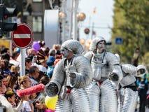 Deltagare av den årliga karnevalet av Adloyada som går på styltor som kläs som robotar i Nahariyya, Israel Arkivfoto