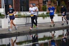 Deltagare av maraton för Moskva 6 Vattenreflexion i en pöl royaltyfria foton