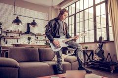 Deltagare av rockbandet som har repetition i vardagsrummet arkivfoto