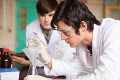 Deltagare i kemi som gör ett experiment royaltyfria foton