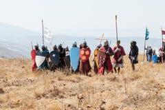 Deltagare i rekonstruktionen av horn av den Hattin striden i 1187 iklädda korsfarare passar, förbereder sig att driva tillbaka en fotografering för bildbyråer