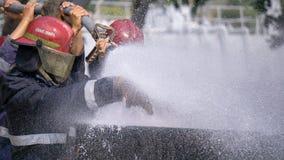 Deltagare i utbildning för brandstridighet släcker enorm brand med vattenvattenposten royaltyfria bilder