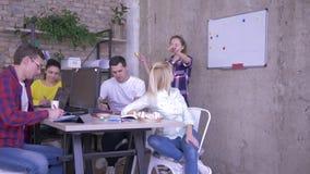 Deltagare i utbildning lär ny expertis på tabellen i modernt kontor som lyssnar till den kvinnliga mentorn nära whiteboarden och, stock video