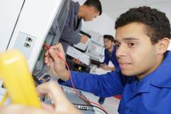 Deltagare i utbildningelektriker som lär deras handel royaltyfria foton