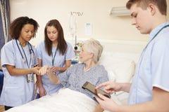 Deltagare i utbildningsjukvårdpersonal vid kvinnliga patients säng i sjukhus royaltyfri fotografi
