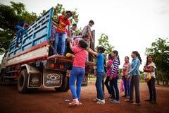 Deltagare som får på en lastbil som används som skolbussen Arkivfoto