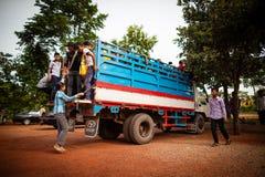 Deltagare som får på en lastbil som används som skolbussen Arkivfoton