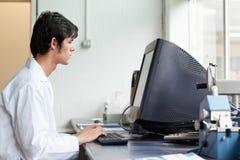 Deltagare som fungerar med en bildskärm arkivbild