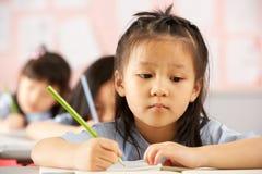 Deltagare som fungerar på skrivbord i kinesisk skola arkivbilder