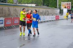 Deltagare som hjälper annan grabb som lossar medvetenhet under av `-Interipe Dnipro den halva Marathonrace `en, arkivbild