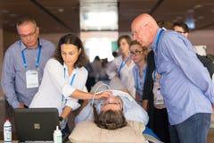 Deltagare som lär nya ultraljudtekniker på medicinsk kongress royaltyfri fotografi