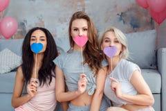 deltagare Unga kvinnor hemma som sitter tillsammans på mun för golvbeläggning med att le för hjärtafotostöttor som är skämtsamt arkivfoton