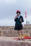 Deltagaren av festivalen som kläs som clown, visar hans konst Royaltyfri Foto
