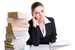 Deltagaren som lärer med högen av, bokar på skrivbordet Arkivbilder