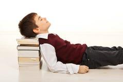 Deltagarepojke som sovar på böcker Royaltyfri Foto