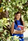 Deltagareståenden på skolar, den lyckliga unga kvinnan med universitetar bo Arkivbild