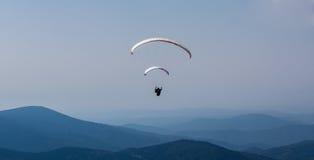 Deltaplane au-dessus de la montagne contre le ciel bleu image stock