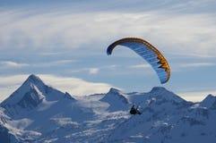 Deltaplane de l'hiver au-dessus des crêtes de montagne Photographie stock