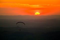 Deltaplaning in zonsondergang stock afbeelding