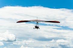 Deltavliegenvlucht in blauwe hemel met wolken Stock Foto's